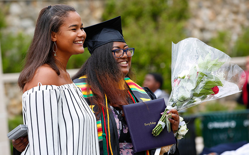 Curry College Class of 2018 graduate smiles for a photo with her sister