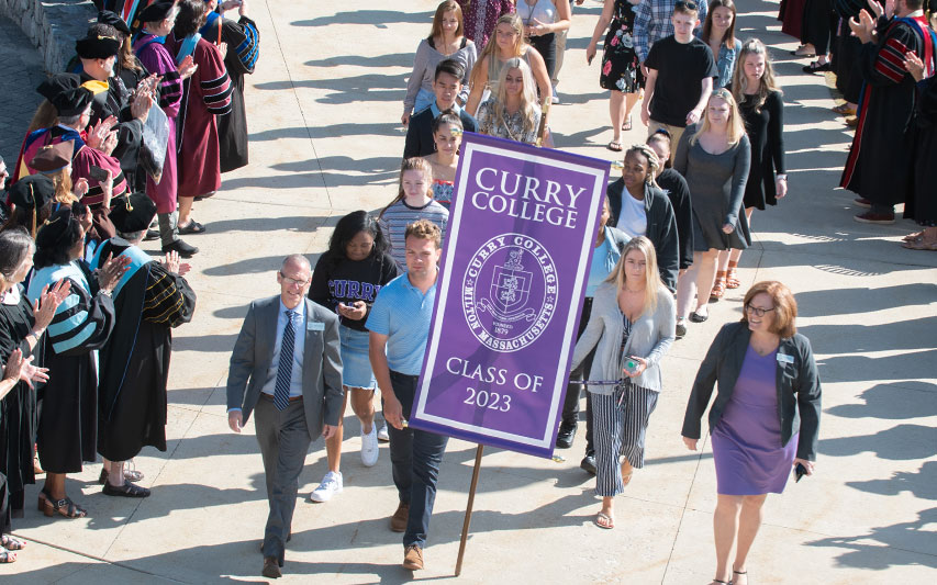 Curry College faculty and staff line the walkway to the Student Center, applauding members of the Class of 2023