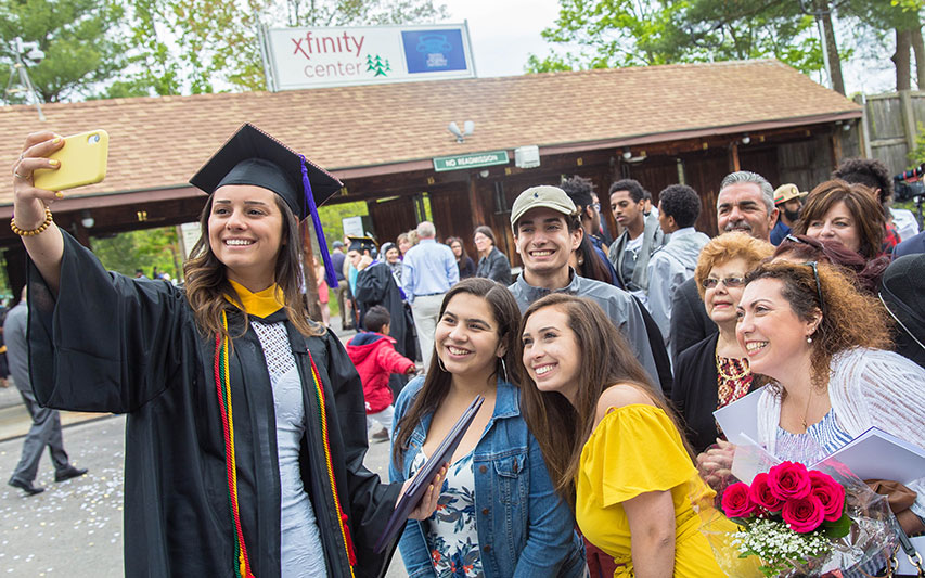 Curry College Class of 2019 graduate smiles for a selfie with her entire family at Xfinity Center