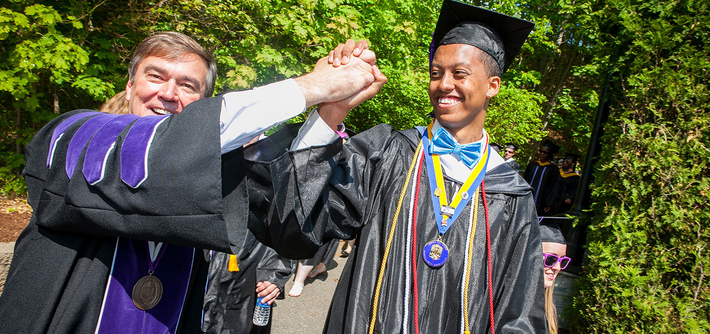 Curry College student gets a high five from the President on Commencement Day