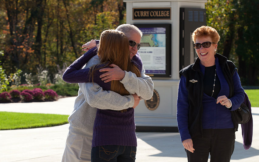 A Curry College student hugs her father on campus