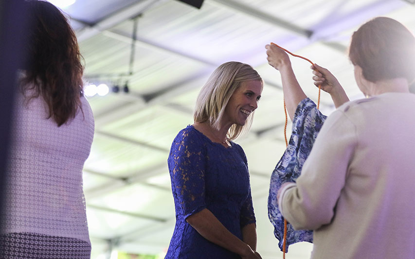 A Curry College School of Nursing student recieves her cord at Nurse Pinning ceremony