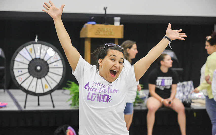 Curry College Orientation Leader poses for a photo with hands in the air