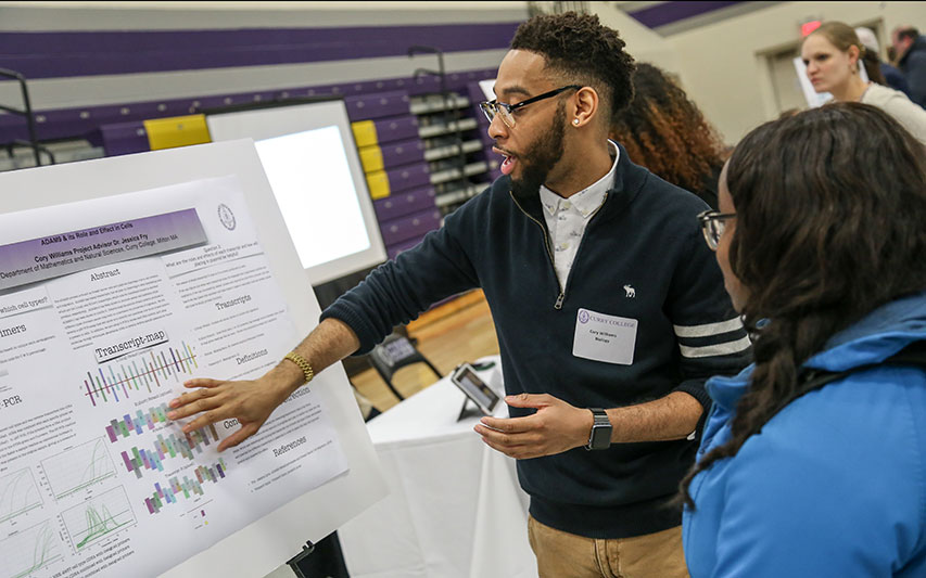 A student presents to a peer at the Curry College Academic Forum