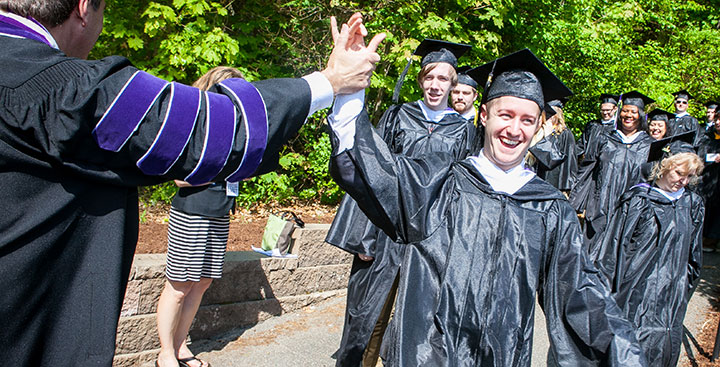 A Curry College graduate receives a high five from the College's President on Commencement Day