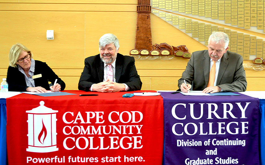 Curry College Provost Dr. David Szczerbacki signs transfer agreement as Dr. Susan Miller, and Dr. John Cox  from Cape Cod Communtiy College look on.