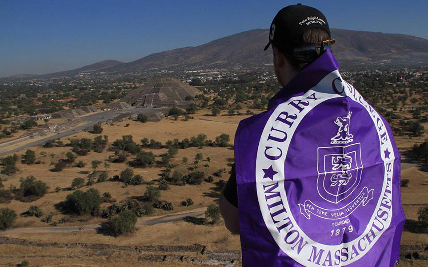 Curry College student in Mexico with College banner.
