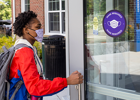 Student walking into Curry College Learning Commons wearing mask
