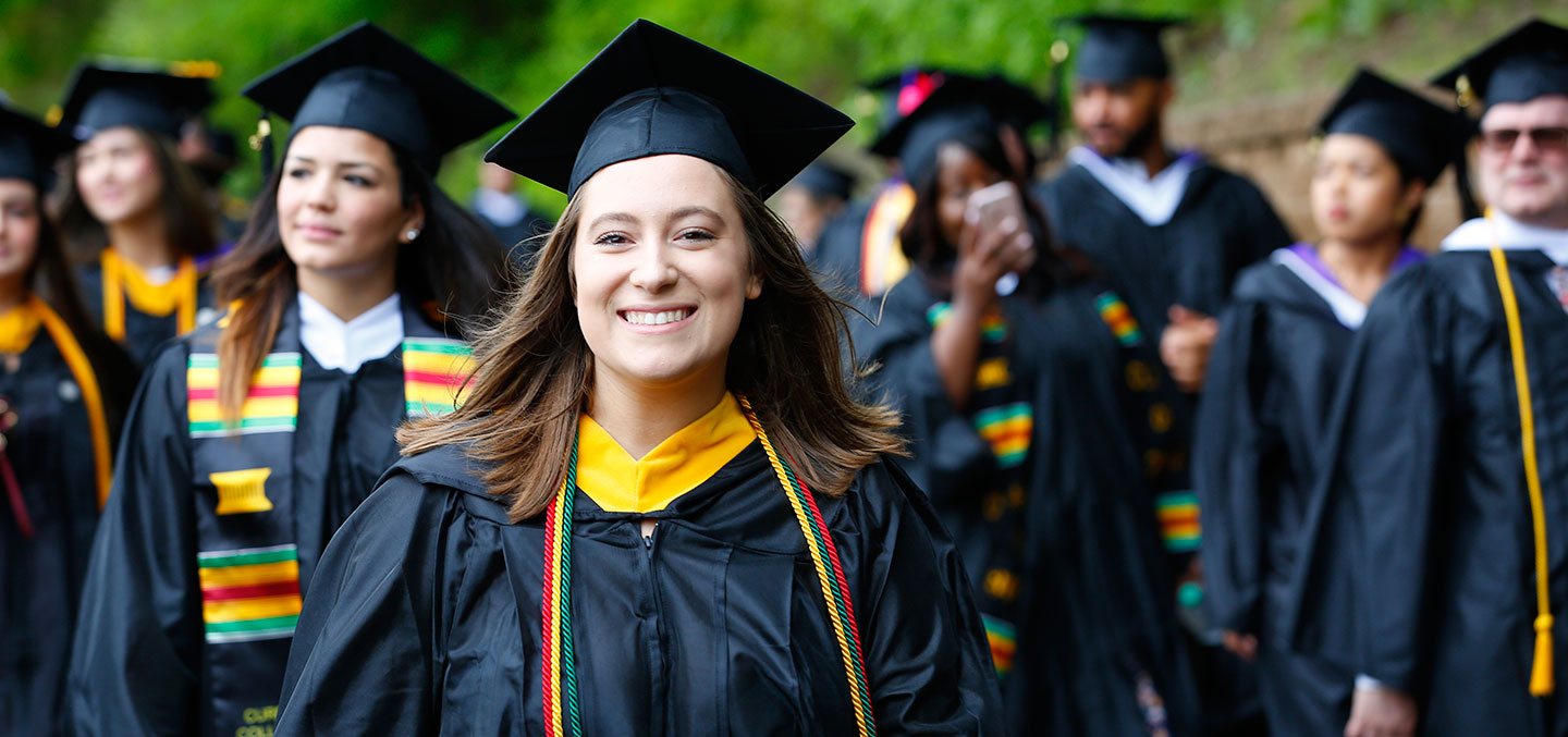 A Curry College student walks on Commencement representing the Curry Fund