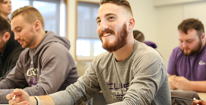 A Curry College student smiling in class