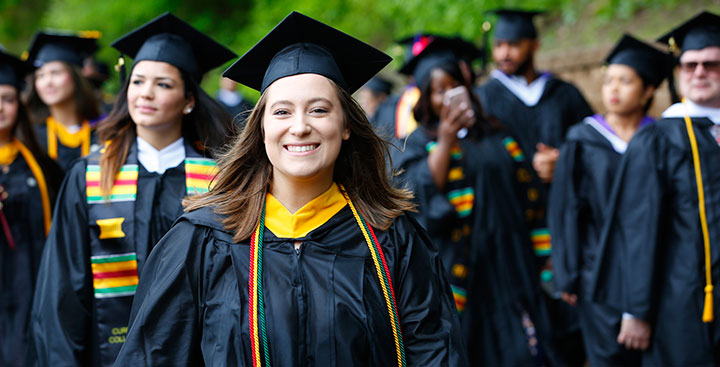 A Curry College student proudly marches at Commencement