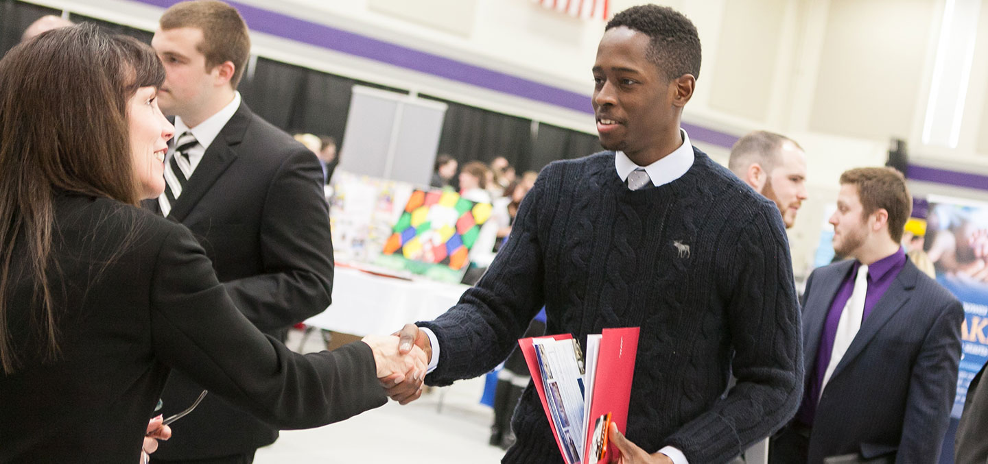A Curry College Center for Career Development Employer partner shakes the hand of a current student