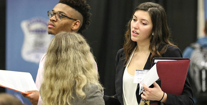 A student speaks with a recruiter at a Curry College Center for Career Development Career and Internship event