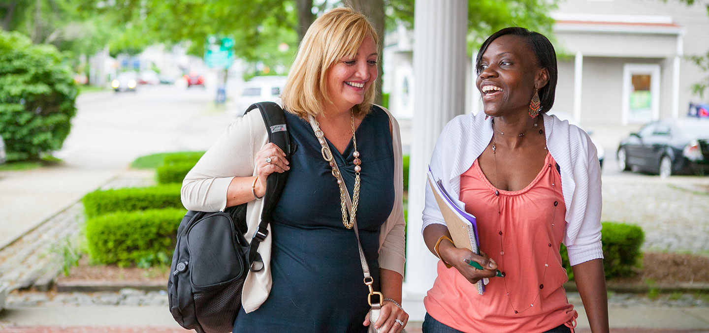 Curry College continuing education degree students laugh while walking on campus