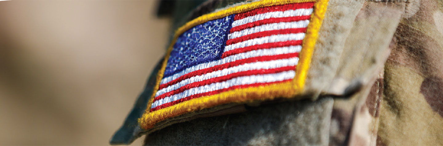 An American flag patch on a military uniform represents veteran students services at Curry College