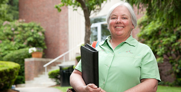 A Curry College Master of Science in Nursing - Nurse Administrator student poses for a photo on campus