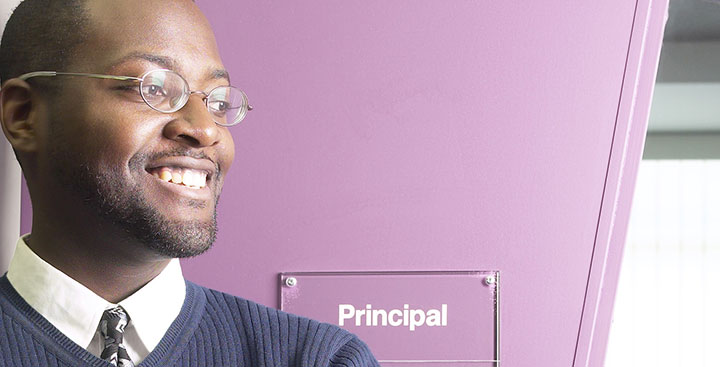 A principal stands outside his office representing the Curry College PSL Certificate program
