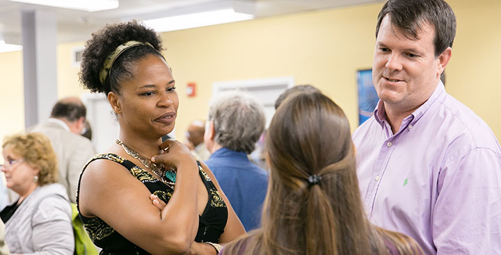Curry College faculty members converse with a First-Year student
