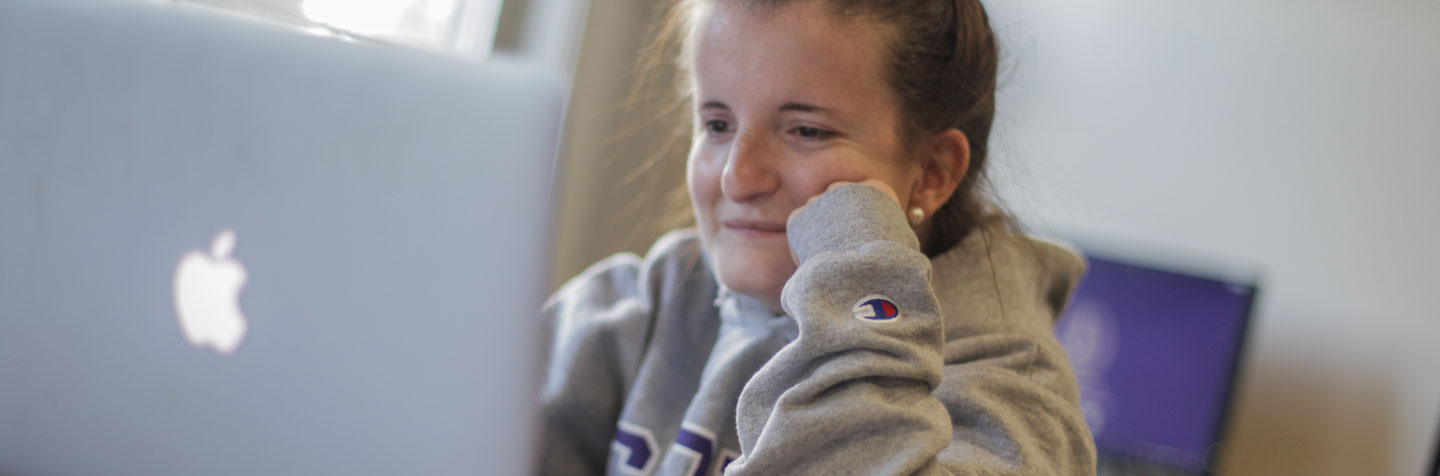 A student on her laptop represents the Curry College Summer PAL Hybrid program