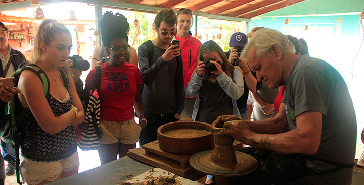 Curry College Study Abroad students in Cuba watch a man make pottery