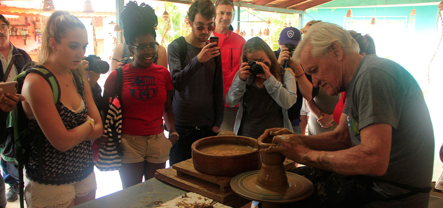 Curry College Students Abroad in Cuba watch a man make pottery