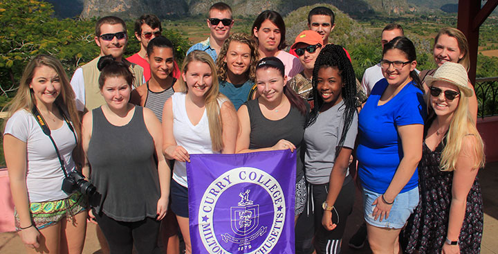 Students pose for a picture with a CurryCollege branded sign in Cuba