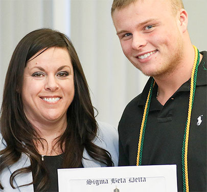 A student receives his Business Honor Society certificate