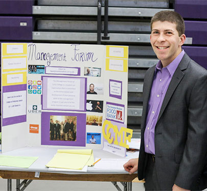 A Curry College Management Forum student poses for a photo
