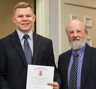 A Curry College faculty member poses with a new member of the COM Honor Society