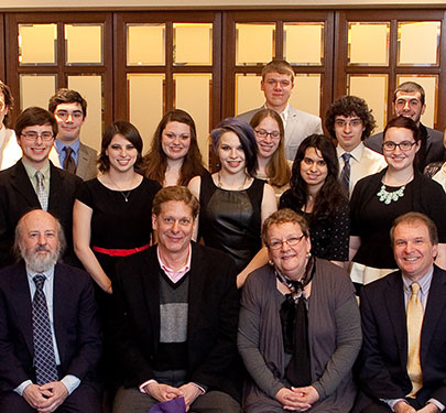 The Curry College COM Scholars and professors pose for a photo at an event