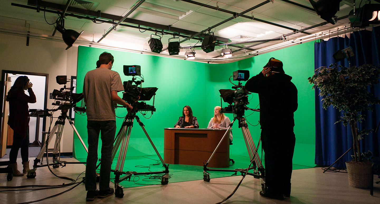 Students run cameras for a television news program at the Curry College Hirsh Communication Center