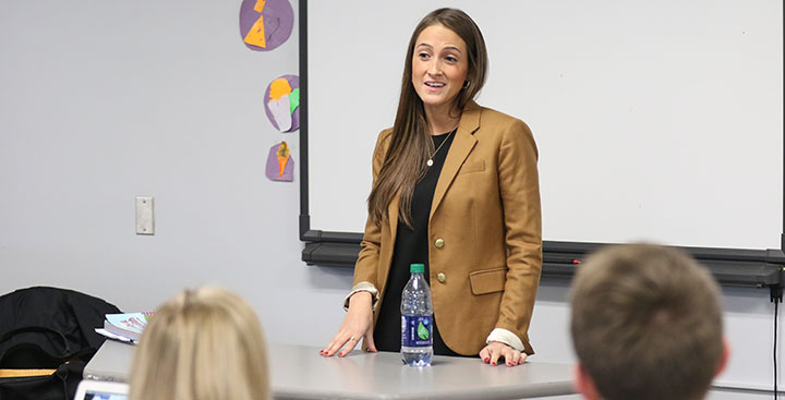 Students and discuss topics in class with professor while pursuing a Public Health and Wellness Degree at Curry College