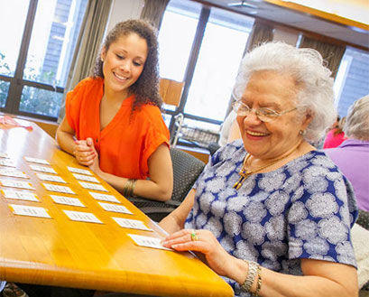 A Curry College nursing student plays cards with an elderly community member