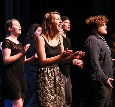 Curry College Sing! student performers belt out a tune on stage