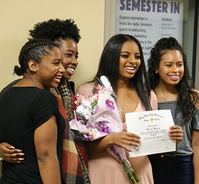 A Curry College student receives her Biology Honor Society certificate