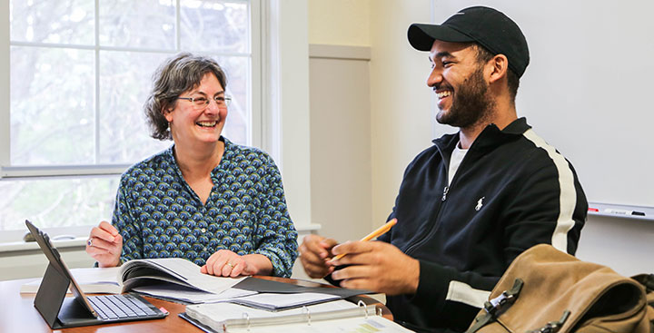 A Program for Advancement of Learning (PAL) professor assists a student with assignments at Curry College
