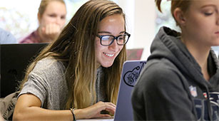 A Curry College Student works on her laptop