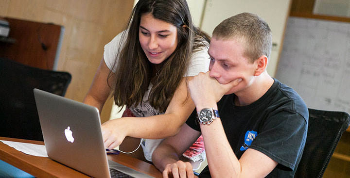 Two students apply to Curry College on their laptop