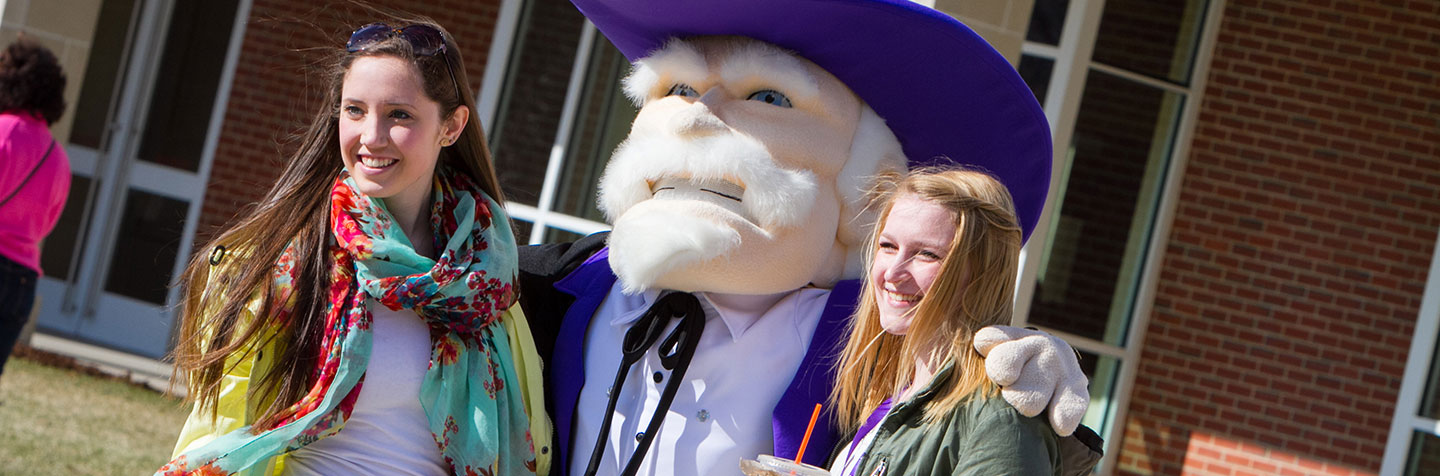Two students pose for a picture with the Colonel at Curry College
