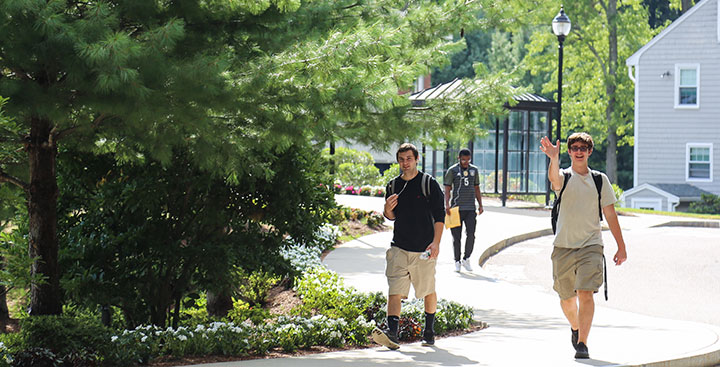 Curry College student smiles and waves as he walks to class with a friend