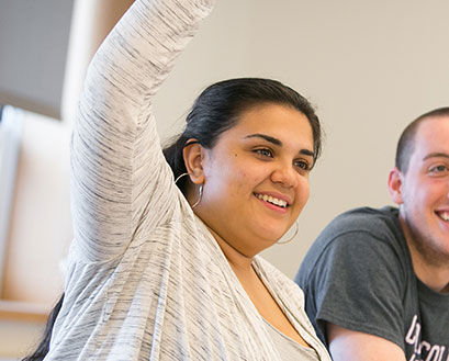 Curry College Student raising her hand in Class