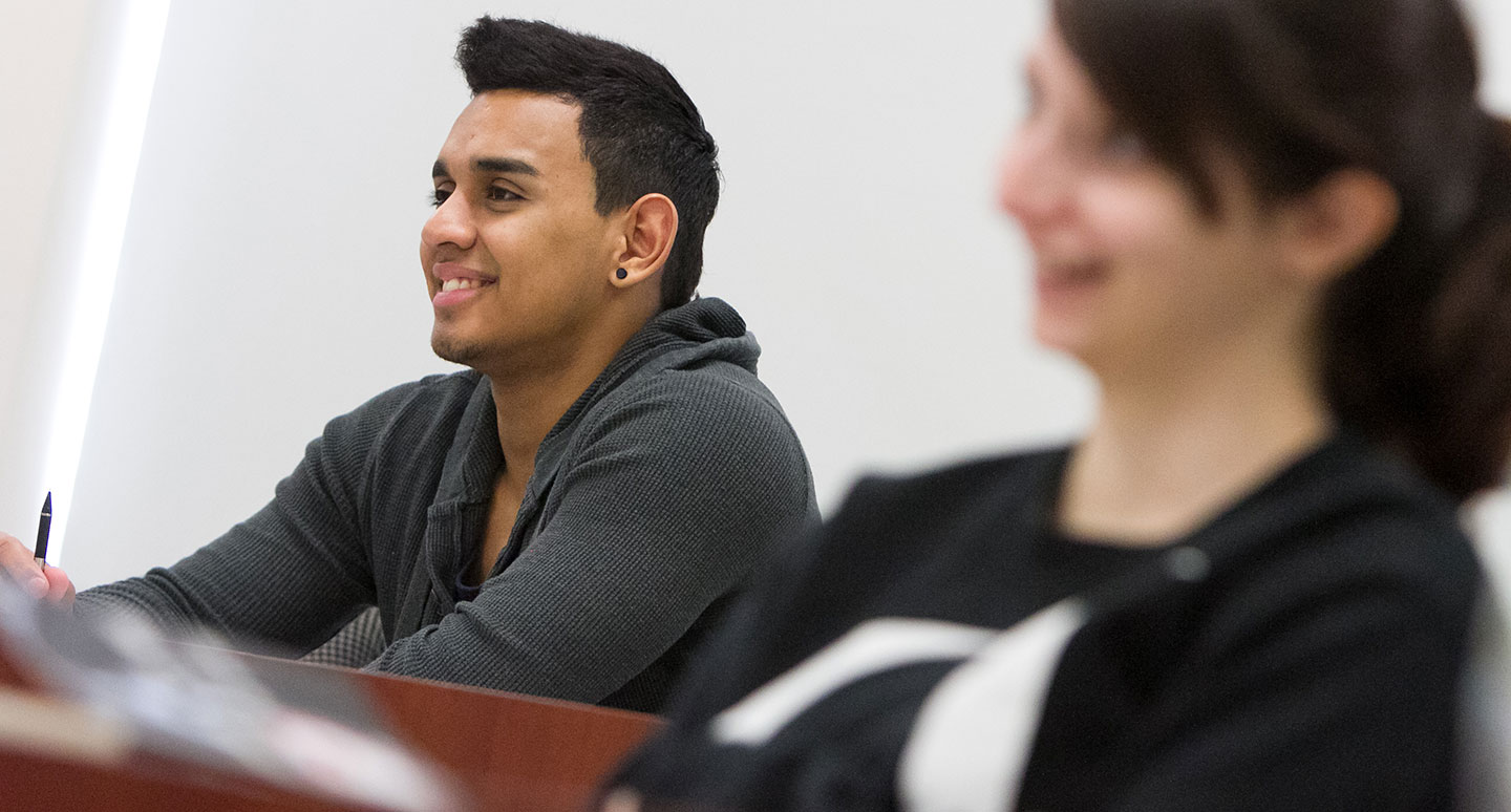Students smiling in class at Curry College
