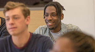 A student smiles in class at Curry College