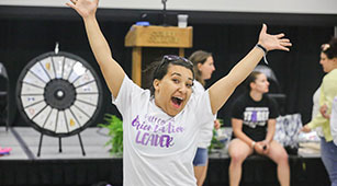 Curry College Orientation Leader waves her hands in the air