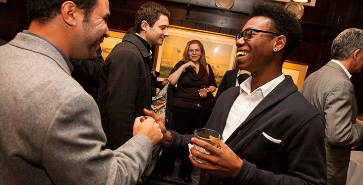 Curry Colege Alumni shake hands at an alumni networking event in New York City