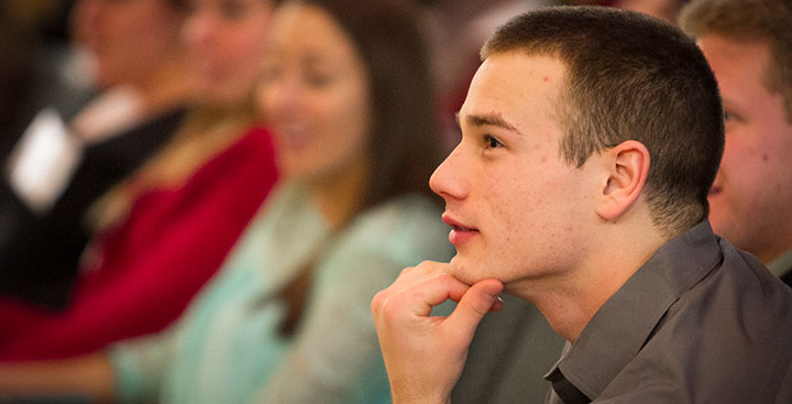 A Curry College student, representing the need for support, smiles in class