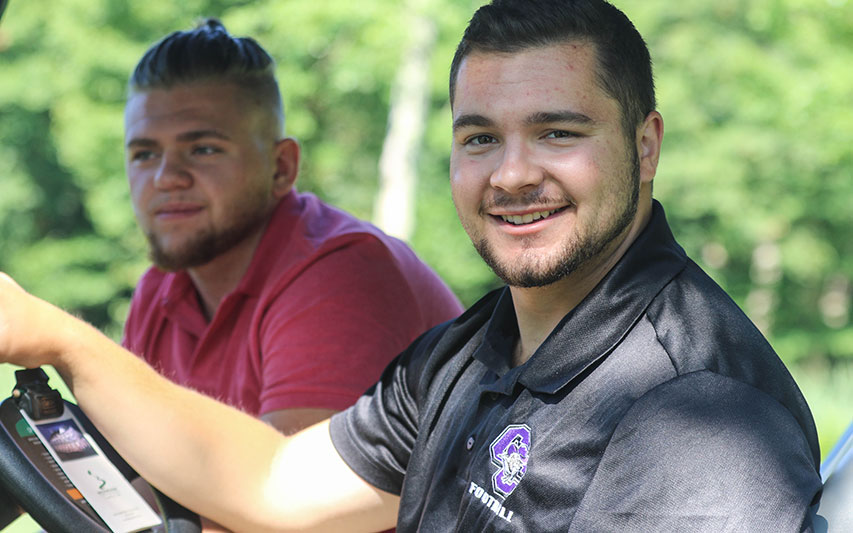 Student Athletes drive a golf cart at the annual Curry College Football Golf Outing