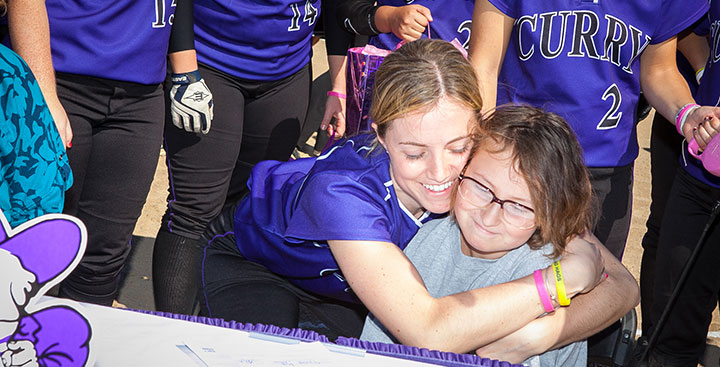 Curry College student-athlete hugs a Team Impact patient