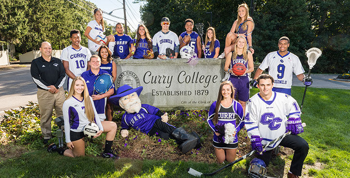 Curry College student-athletes pose at the front gate for a photo