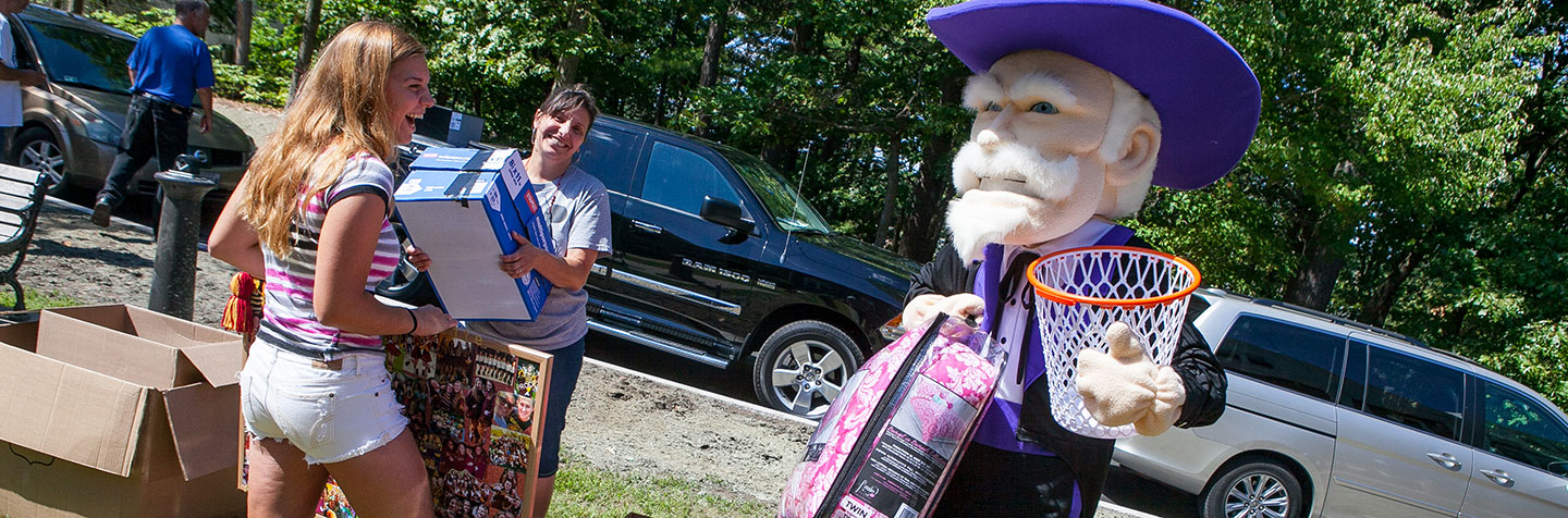A Curry College student and her mother laugh with the Colonel on Move in Day representing Prospective Parents to the College